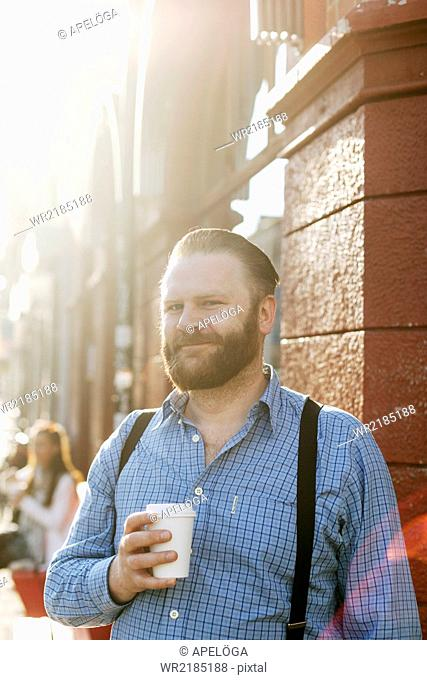 Portrait of smiling businessman holing disposable coffee cup on sidewalk