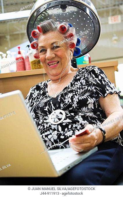 Older woman with laptop and headphones in hair salon, smiling, portrait