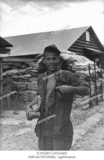 A United States Army serviceman wearing an unbutton utility fatigue shirt, he is smiling and carrying some belongings while walking on base, Vietnam, 1967