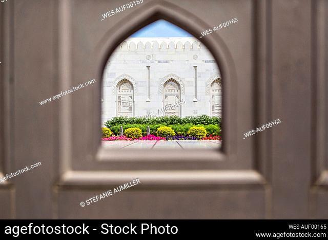 Oman, Muscat, Garden of Sultan Qaboos Grand Mosque seen through arch-shaped window