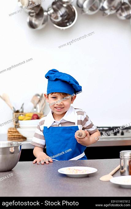 Little boy with blue hat and apron baking