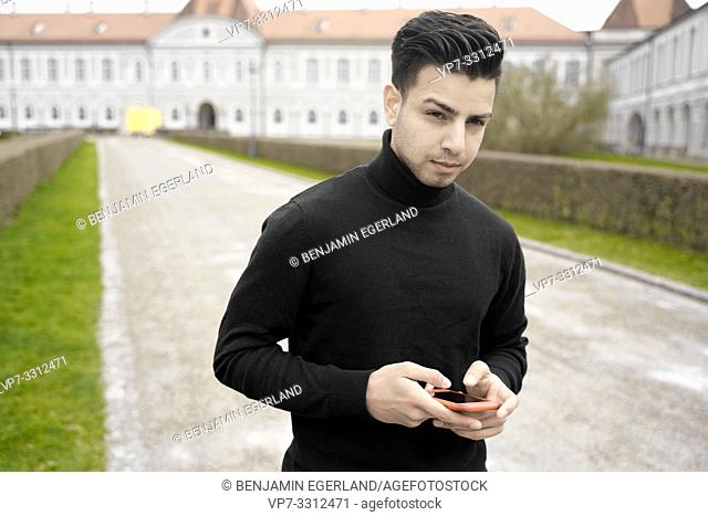 young man with phone in front of aristocratic Nymphenburg Palace, touristic sight, in Munich, Germany
