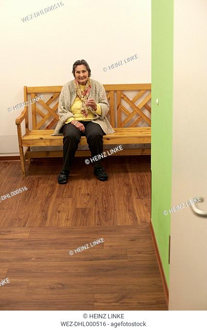 Age demented senior woman sitting on bench in a nursing home