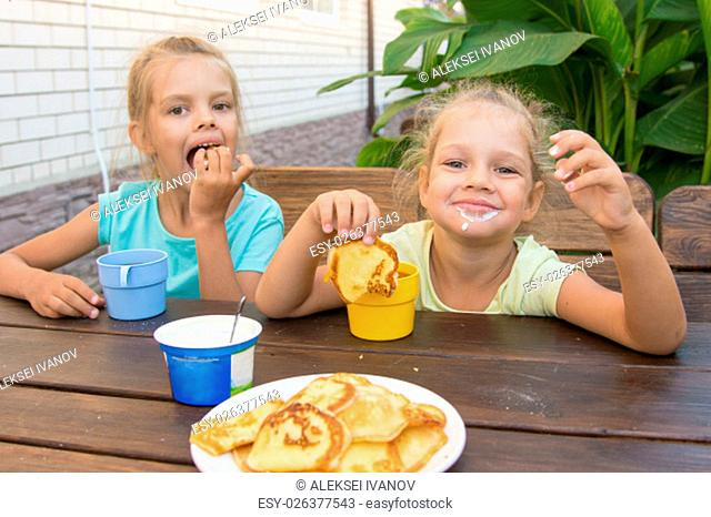 Satisfied children at a table in the courtyard eating pancakes with sour cream
