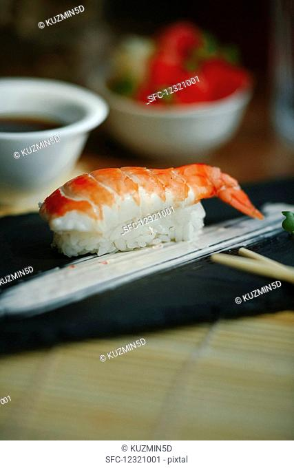 Nigiri sushi with shrimp on a black plate