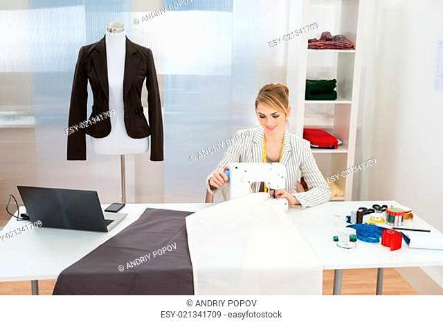 Smiling Fashion Designer Stitching Fabric On Sewing Machine In Studio