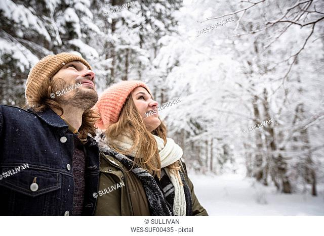 Smiling couple in winter forest watching snow fall