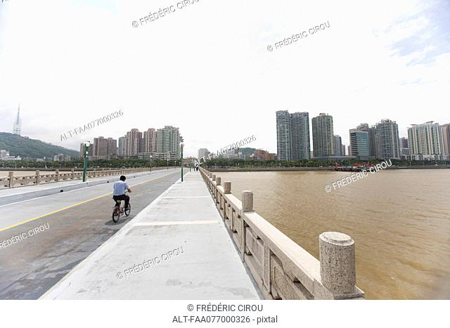 Man riding bicycle on bridge, Shandong province, China