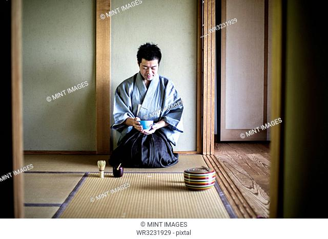 Japanese man wearing traditional kimono kneeling on tatami mat, holding tea bowl, during tea ceremony
