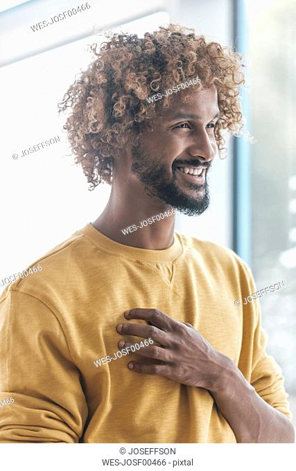 Smiling young man with Afro curls, portrait