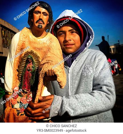 A boy holds an image of Saint Juan Diego during the annual pilgrimage to the Our Lady of Guadalupe Basilica in Mexico City, Mexico