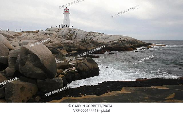 Bagpipes being played and a view of the surf and lighthouse at Peggy's Cove Nova Scotia Canada