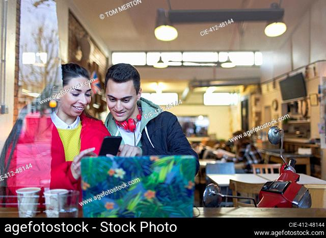 Young couple using smart phone at cafe window