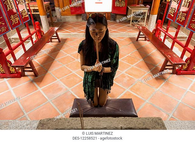 A Chinese young woman praying and offering incense in a Buddhist temple; Shanzidou, Kinmen Island, Taiwan