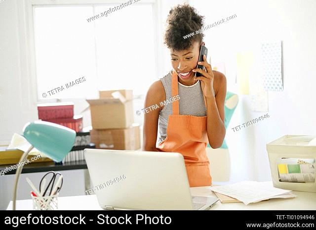 Young woman in home office on the phone