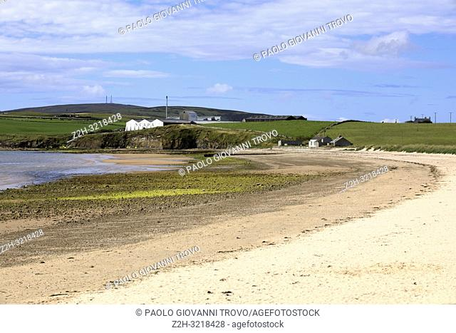 Scapa Bay near Kirkwall in Orkney with the Scapa distillery buildings sitting above the shoreline in the distance, Orkney, Scotland, Highlands, United Kingdom