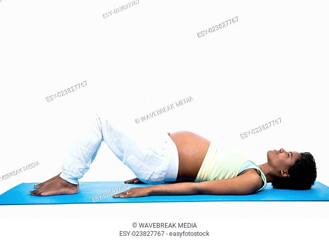 Pregnant woman doing exercise on mat