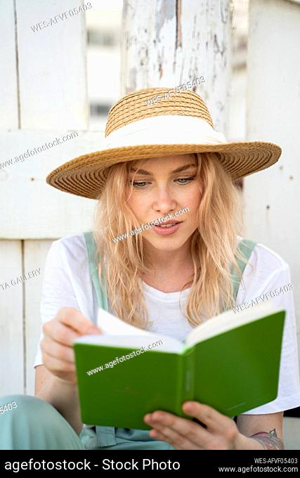 Young woman spending a day at the seaside, reading a book on the beach