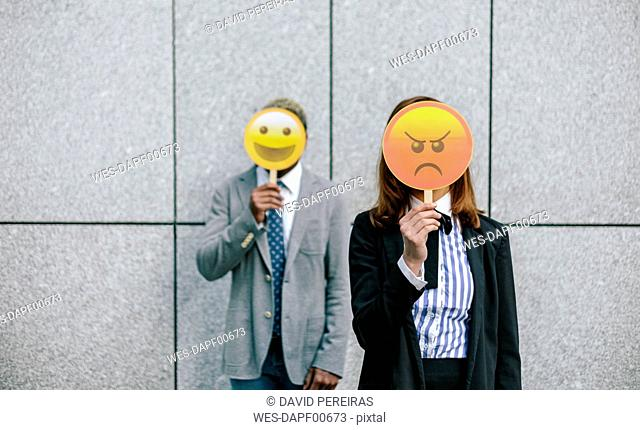 Young businessman and woman covering faces with emoji masks