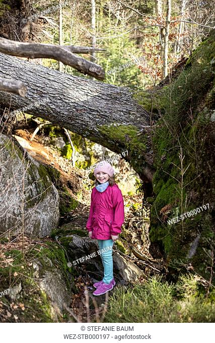 Little girl standing besides an upset tree