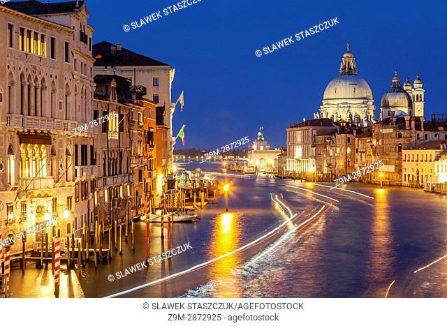 Night falls on Grand Canal in Venice, Italy. Santa Maria della Salute church dome in the distance
