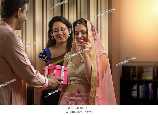 Smiling man presenting gift to his wife