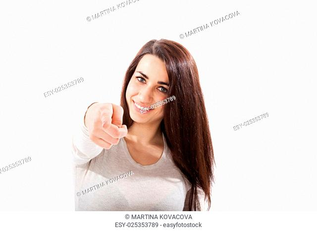 Beautiful brunette pointing on white background. Caucasian woman smiling. Isolated over white background