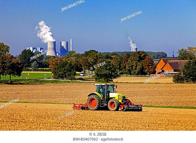 tractor on an acre in front of power station Westfalen, Germany, North Rhine-Westphalia, Muensterland, Lippetal