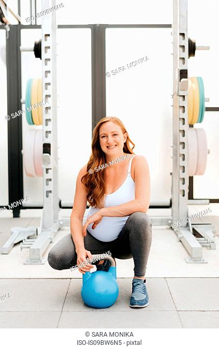 Pregnant woman exercising with kettle bell on balcony