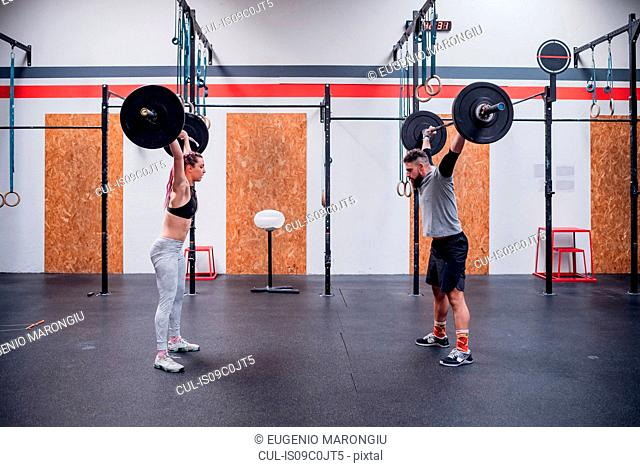 Young couple lifting barbell in gym