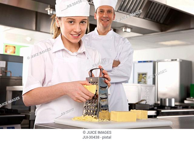 Chef watching trainee grating cheese in commercial kitchen