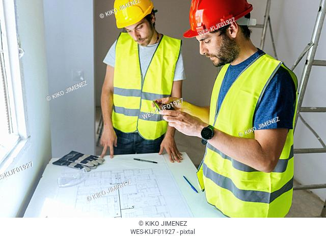 Workers taking a picture of the plan with mobile phone