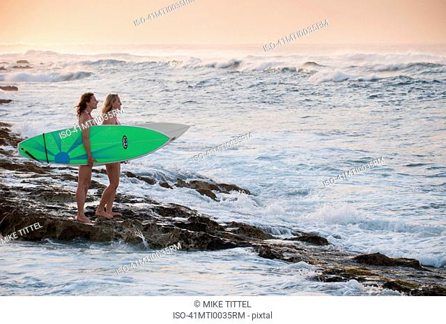 Surfers carrying surfboards on beach