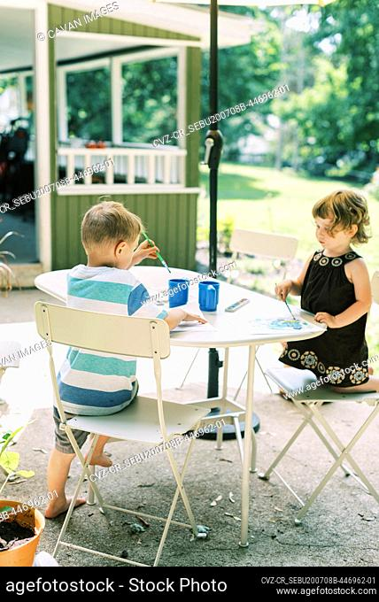 Little artists painting with watercolors outside on the patio