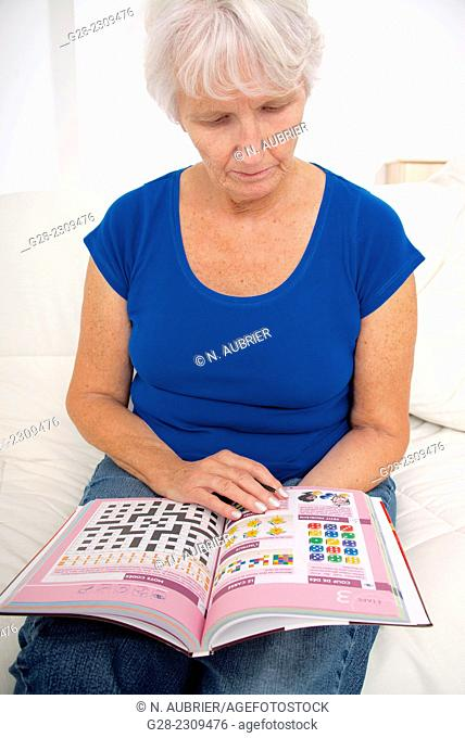 Senior woman in blue, exercising her brain for Alzheimer with an exercise book