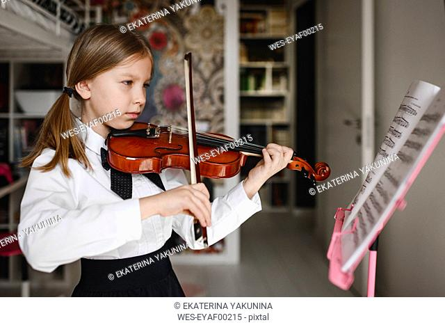 Girl playing violin looking at music stand at home