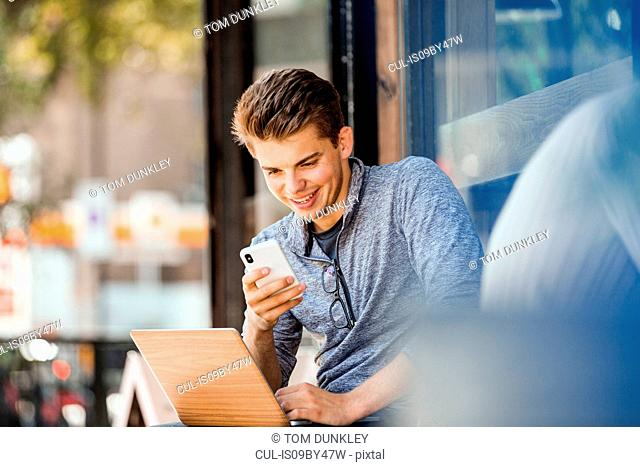 Young man using smartphone and laptop at cafe