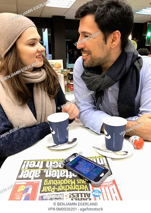 couple looking at each other, taking a break at table at gas station's café with newspaper Bild and phone laying on table and paper cups of coffee in Munich