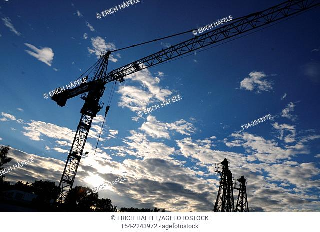 Silhouettes of construction cranes at a construction site in Memmingen, Germany, Bavaria