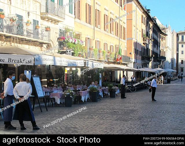 18 July 2020, Italy, Rom: Waiters and waitresses wait for customers in front of the restaurant in Piazza Navona. The number of foreign tourists in Italy's...