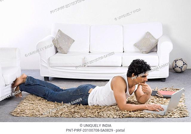 Man using a laptop on the floor