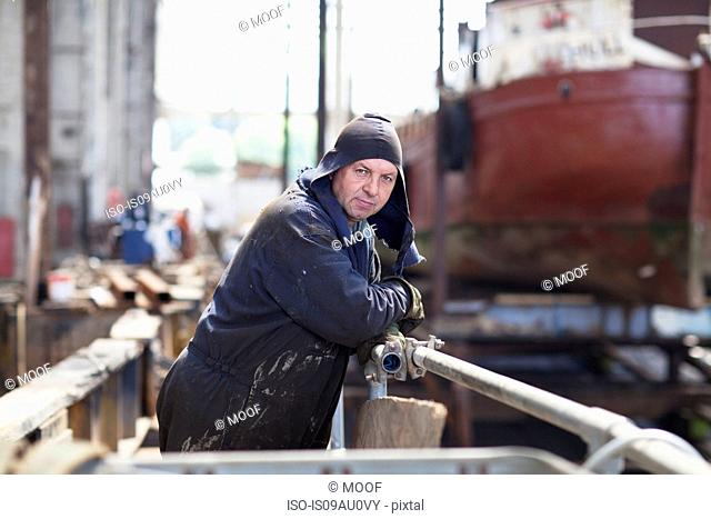 Portrait of worker leaning against railings in shipyard workshop