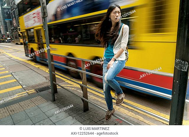 Chinese young woman seated on handrail in a street with a two floors bus passing behind her; Hong Kong, China