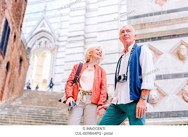 Tourist couple with camera and smartphone by city stairway, Siena, Tuscany, Italy