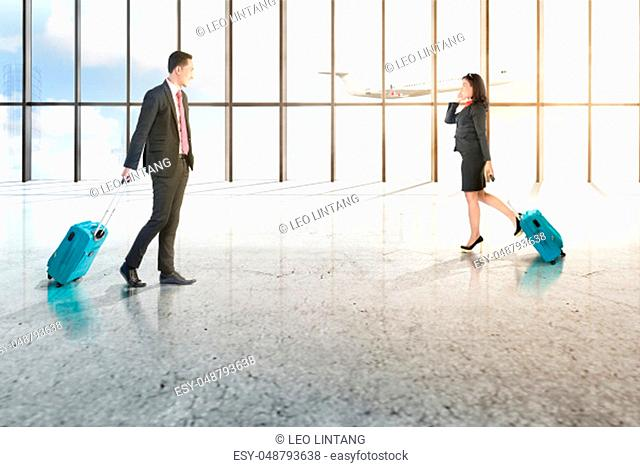 Attractive two asian business people with mobile phone and blue suitcases walking on the airport hall with window of glass and flying airplane over blue sky...