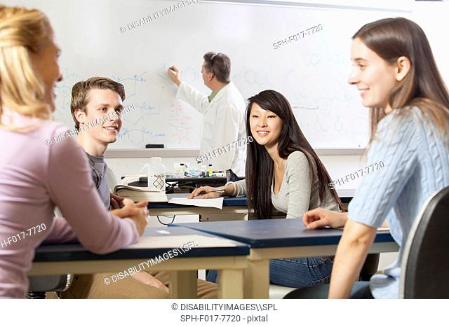 Students talking in an engineering class while the professor is writing on the white board