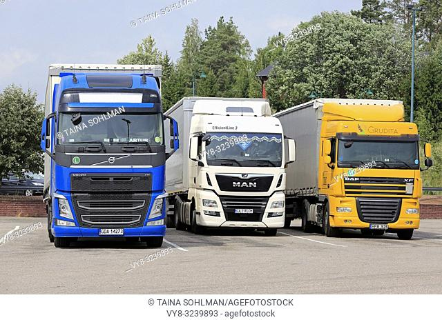 Salo, Finland - July 29, 2018: Volvo FH, MAN and DAF XF transport trucks from Poland, Ukraine and Lithuania parked on a Finnish truck stop in summer