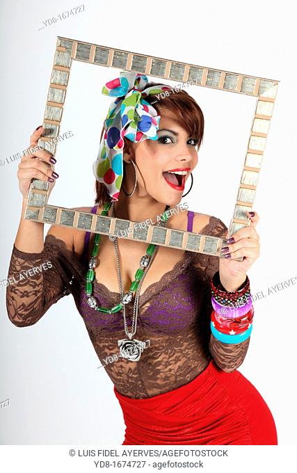 Young woman posing happy through a special frame in the Studio