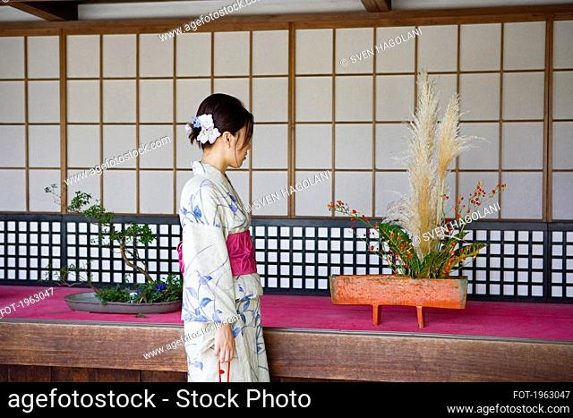 Young Japanese woman in kimono looking at ikebana flower arrangements