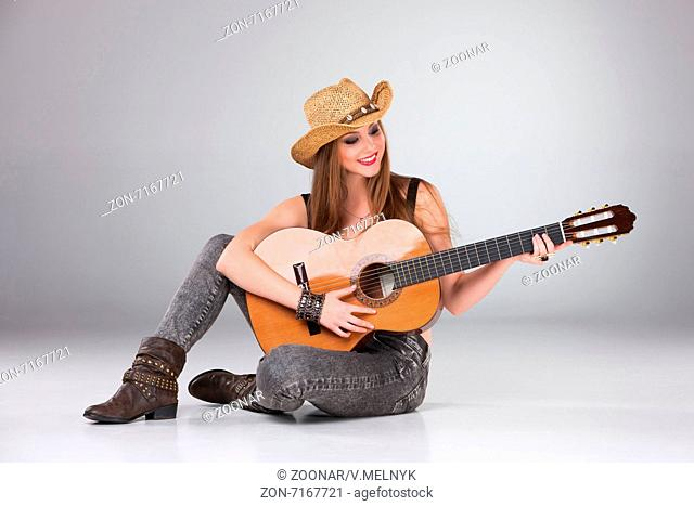 The beautiful girl in a cowboy's hat and acoustic guitar